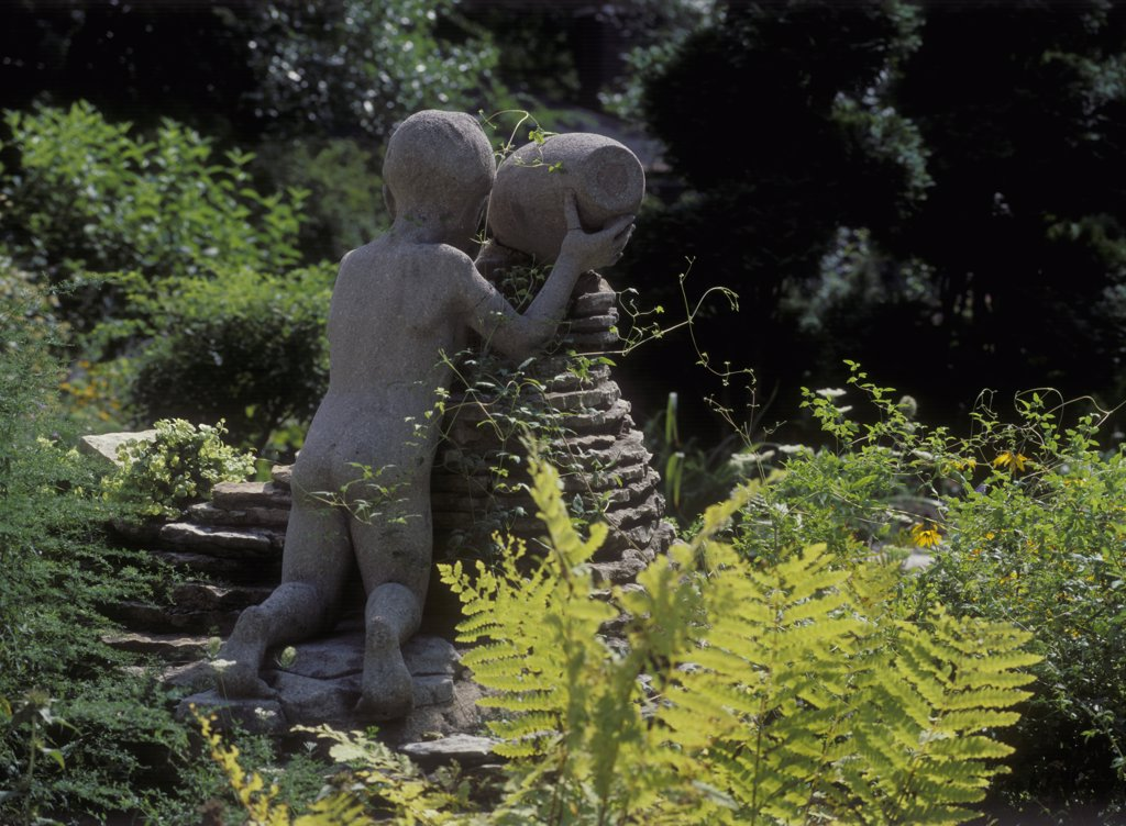 GARDENS: 1930s garden, life size statue of a boy pouring water from an urn onto the waterfall cascade, backside of sculpture, ferns, summer. : Stock Photo