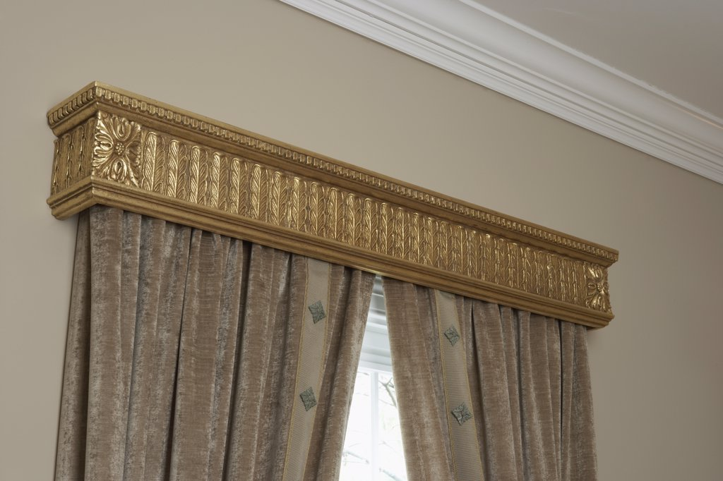 WINDOW  TREATMENTS: gold cornice above silk drapes, beige wall, white crown molding : Stock Photo