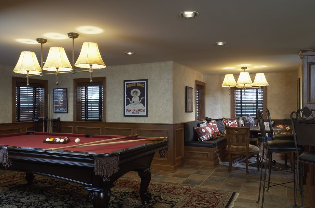 BASEMENT   recreation room with billiards table and eating area, bar stools pulled up to bar out of camera range on the right, louvered wooden blinds, tile floor : Stock Photo