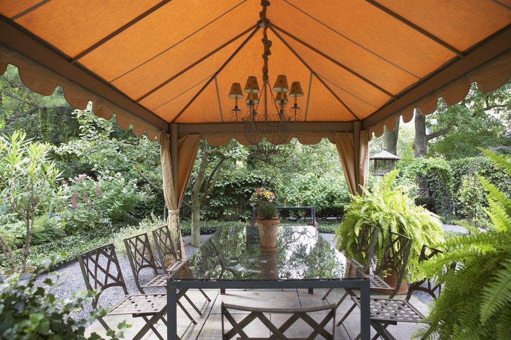 GAZEBOS: Garden, patio, fabric gazebo, chandelier, rectangular dining table , Boston ferns garden surrounds : Stock Photo