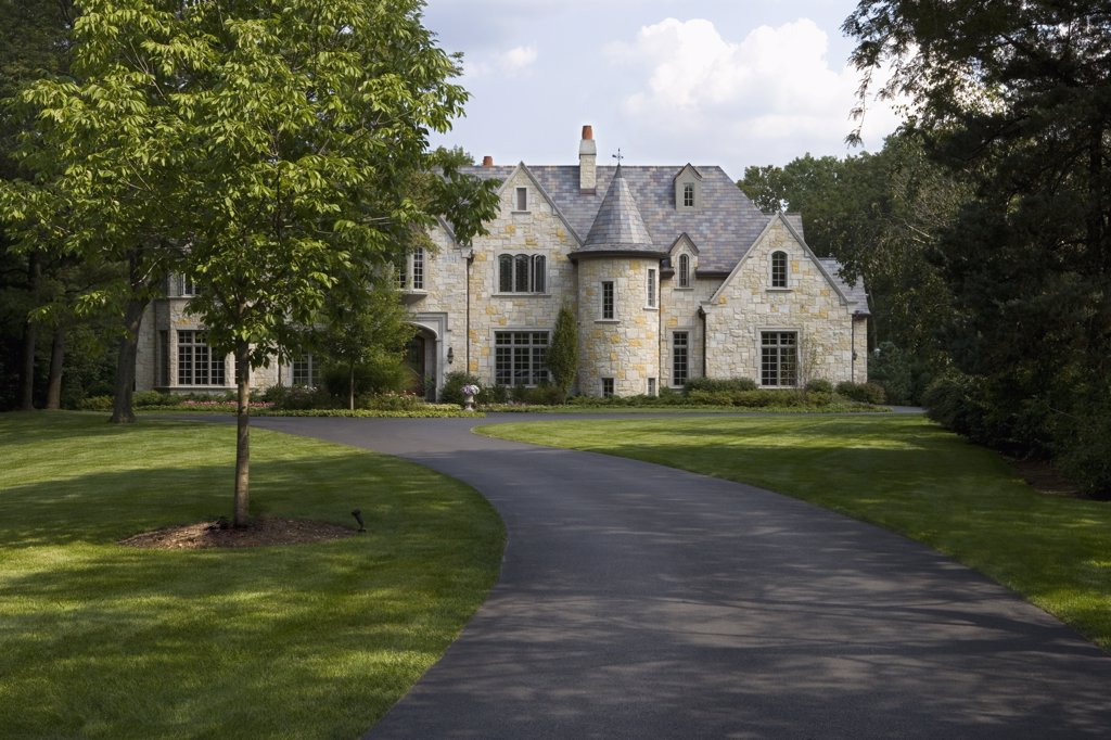 EXTERIORS: Blacktop driveway to French Normandy stone home : Stock Photo