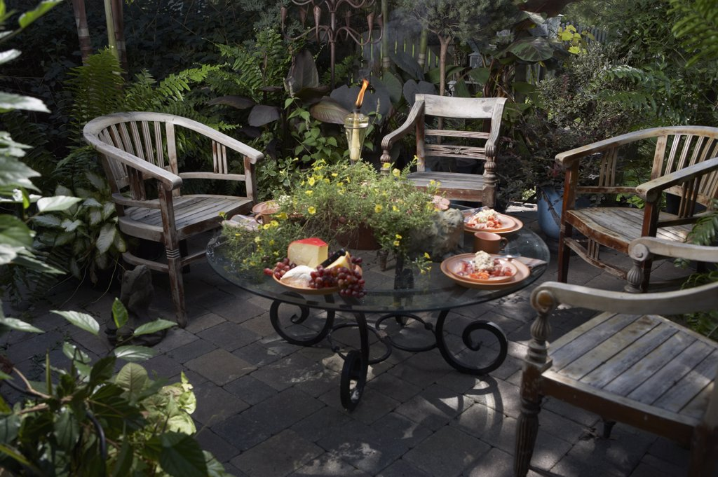 Stock Photo: 4053-11964 PATIO AREA: Four teak British colonial style furniture, glass top coffee table, container gardens cheese plate, tiki torch , potted plants