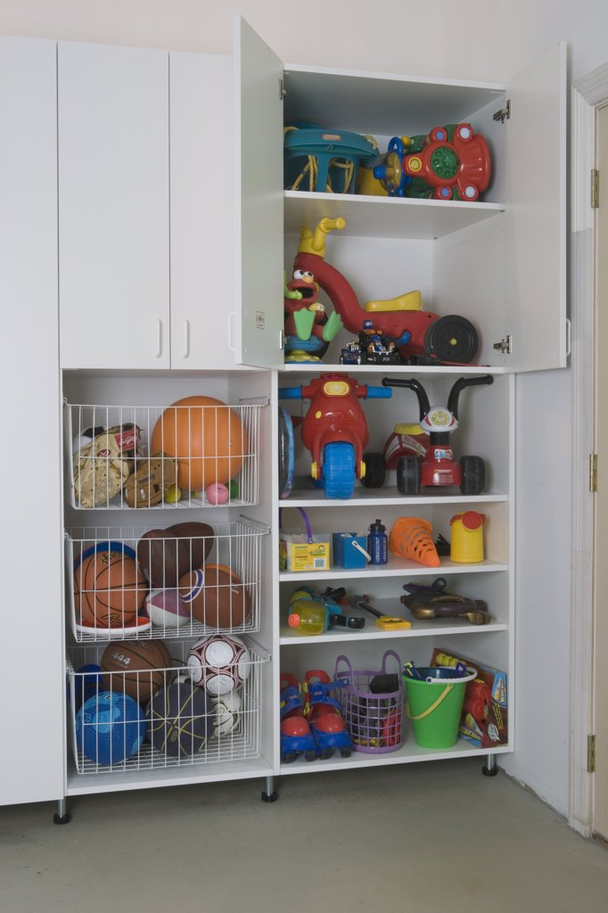 Stock Photo: 4053-11984 GARAGE STORAGE: clean and organized after pictures, storage  cabinet detail, wire pull out bins filled with balls, open doors on cabinet to reveal toys, all doors open