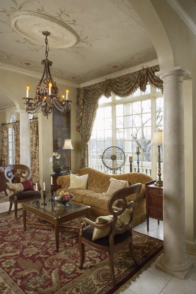 LIVING ROOMS; sitting area architectural trim painted ceiling, columns floral swag and jabot drapes, antique chandelier, gold sofa, red area rug on tile floors, : Stock Photo