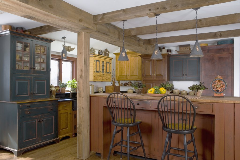 KITCHENS: David TO Smith furniture style  historic looking cabinets, two tiered work island and eating area with Windsor style barstools,  punched tin pendant lights by tinsmith  Michael P Terragna, mustard, red and dark green paint finishes, peppers : Stock Photo