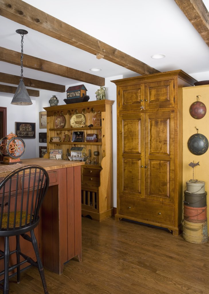 Stock Photo: 4053-12063 KITCHENS: period style , furniture style cabinets by David Smith, cupboard hides ovens, stack of colorful firkins, tin pendant lighting, display cabinet with Noah's Arks, part of kitchen island to left