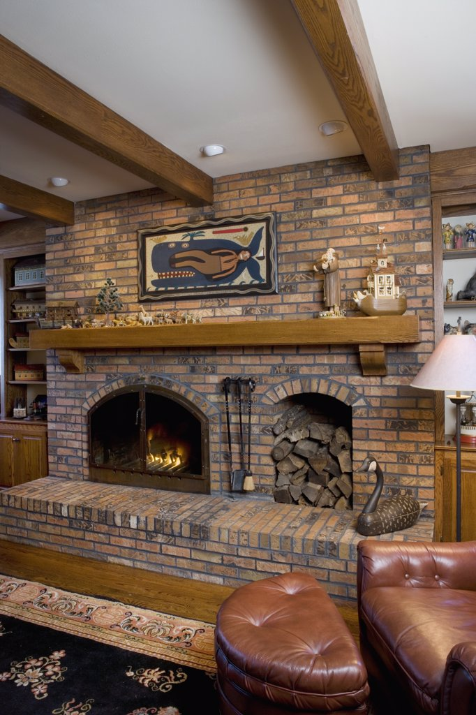 FIREPLACES: raised hearth brick fireplace with built in wood box, log mantel with folk art Noah's Arks and painting of Jonah and the Whale leather ottoman and chair to right : Stock Photo