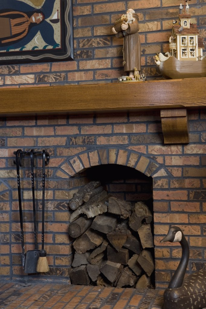 Stock Photo: 4053-12075 FIREPLACE DETAILS: brick hearth, built in place for stacked wood, fireplace tools, goose decoy, wood mantel, with Noah's Ark