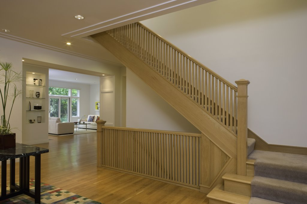 STAIRWAYS: Contemporary Prairie style home with plaster crown molding, open concept rooms, large entry hall, light stained wood stairs and floor, built in display shelves house art glass and pottery : Stock Photo