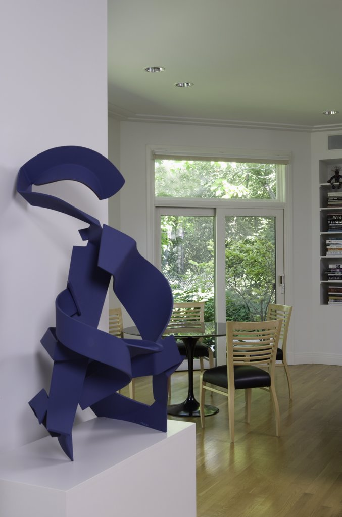 Stock Photo: 4053-12096 LIVING ROOM DETAILS: A blue metal sculpture ' Blue Geisha' sits on a pedestal, light wood floors in contemporary home, transom over sliding doors, built in book shelves to right sitting area