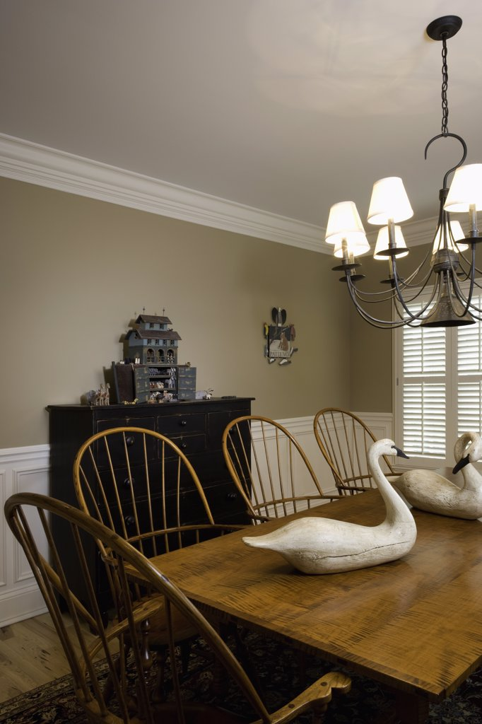 DINING ROOM;  Windsor chairs, swan decoys, chandelier, Noah's ark on cabinet, crown molding, and dado contemporary country : Stock Photo
