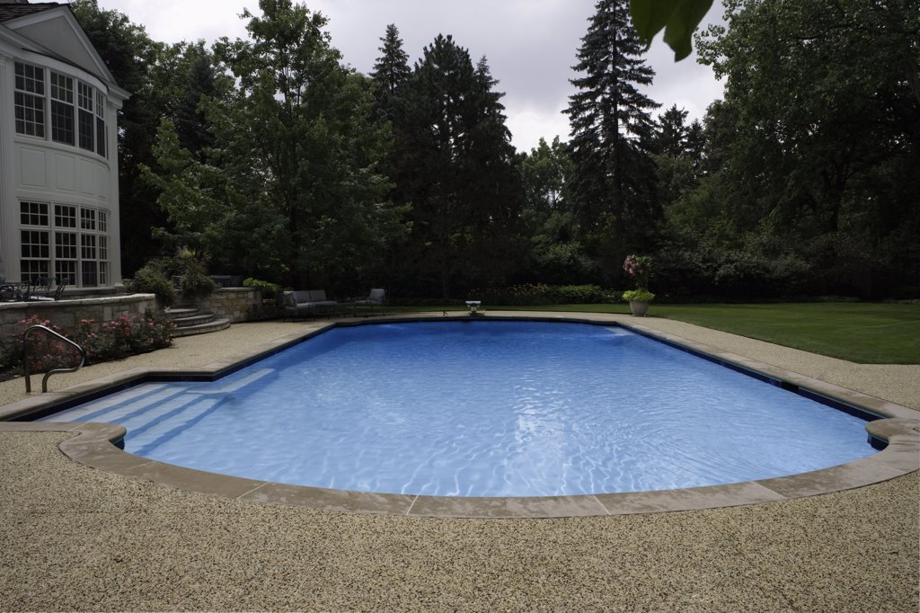 SWIMMING POOLS: looking straight over pool, aggregate patio, far left a corner of home : Stock Photo