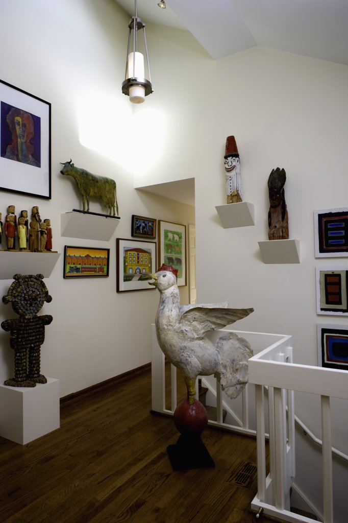 Stock Photo: 4053-12468 ENTRY HALL; collection display of new and old folk art, some carved some painted, antique tin chicken, cow weathervane