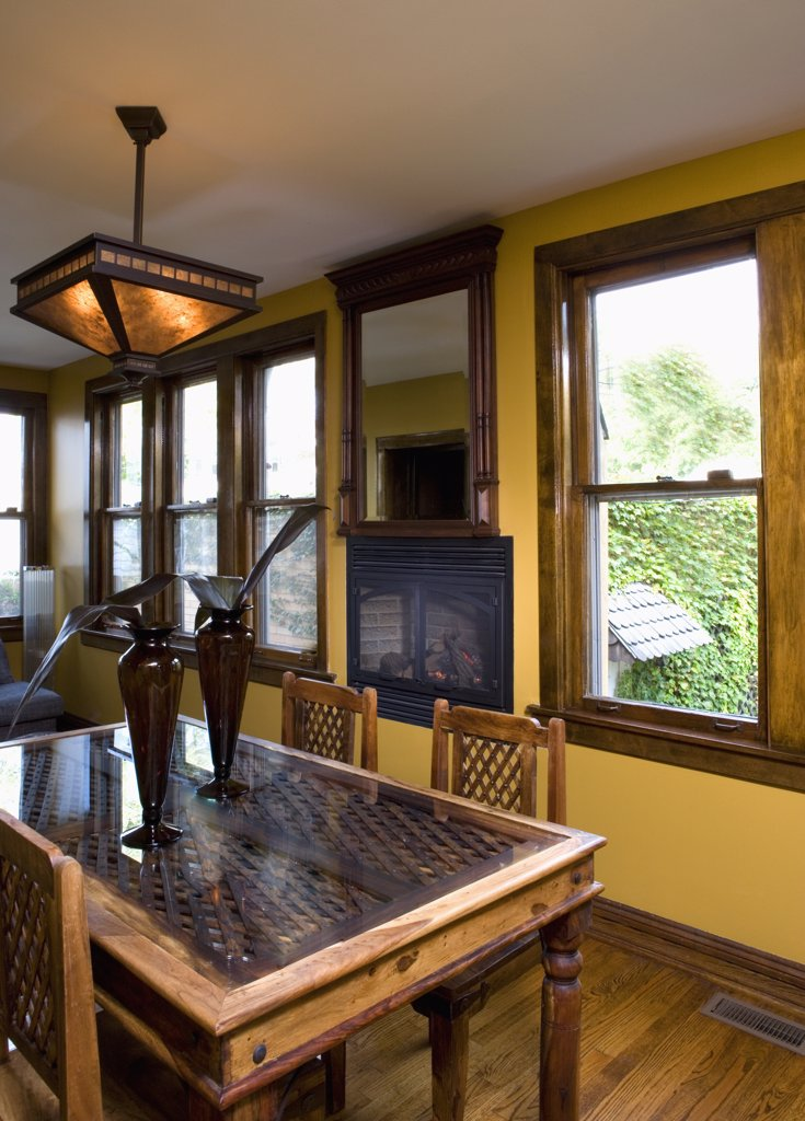 Stock Photo: 4053-12484 EATING AREA: breakfast room, gas fireplace in wall under mirror, antique East Indian door recycled  as a table top, yellow walls