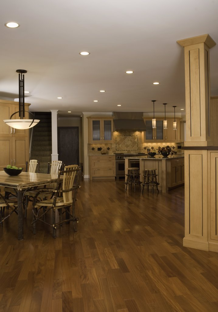 KITCHEN: expansive wood floors connect the twig dining table and chairs, with the kitchen area, large island with Craftsman style pendant lighting, maple cabinets, tile backsplash, column wall divider : Stock Photo