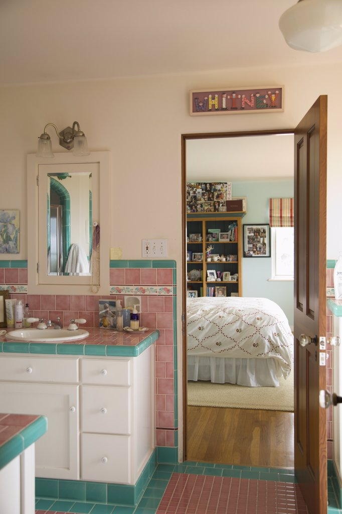 Pink and blue tiled bathroom between bedrooms : Stock Photo