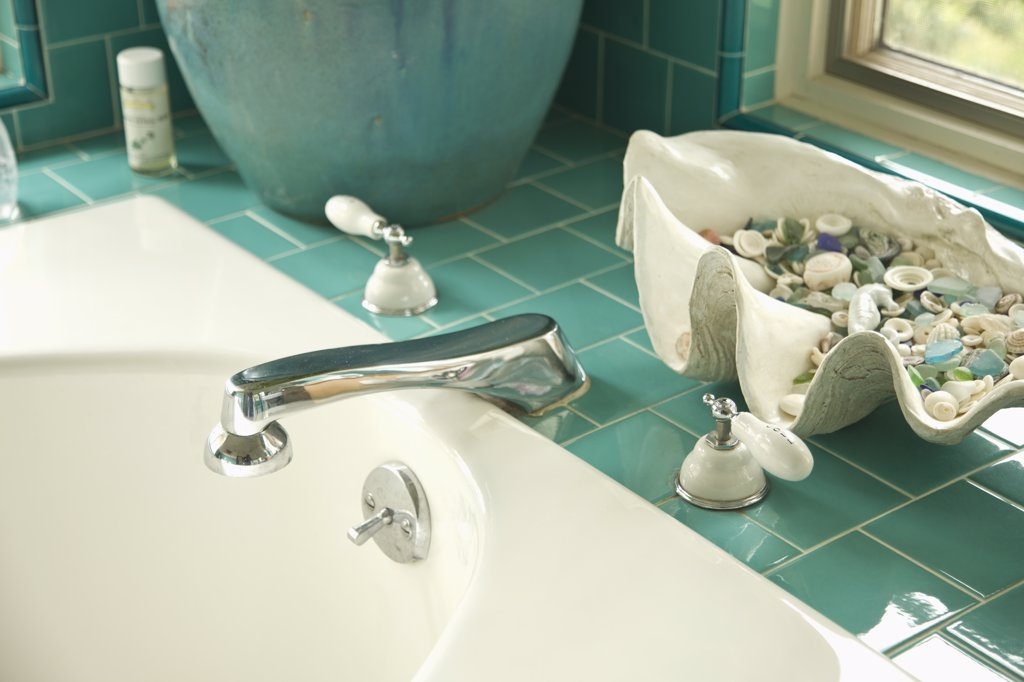 Stock Photo: 4053-14096 Decorative shells on aqua tile bathroom counter near sink