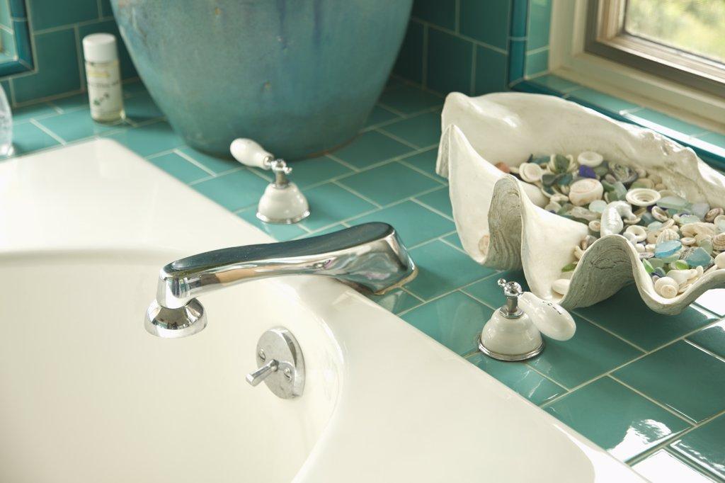 Decorative shells on aqua tile bathroom counter near sink : Stock Photo