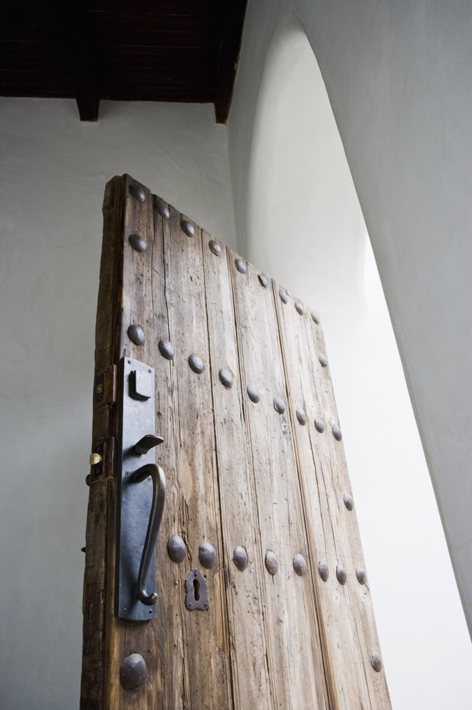 Old wooden door in arched doorway : Stock Photo