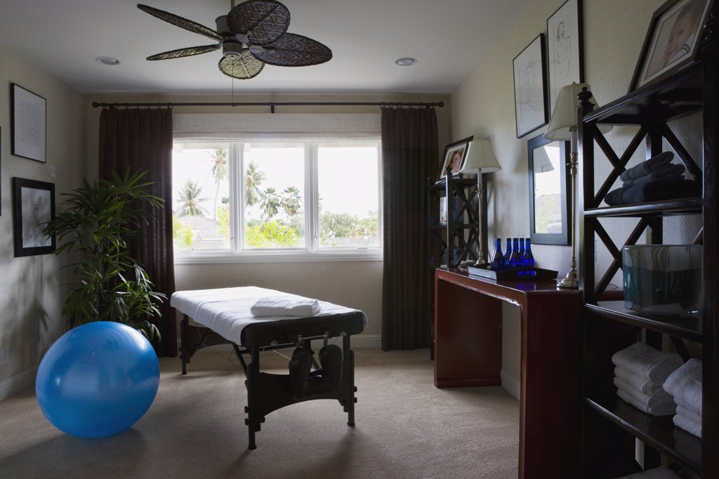 Home spa room with massage table and Swiss ball : Stock Photo