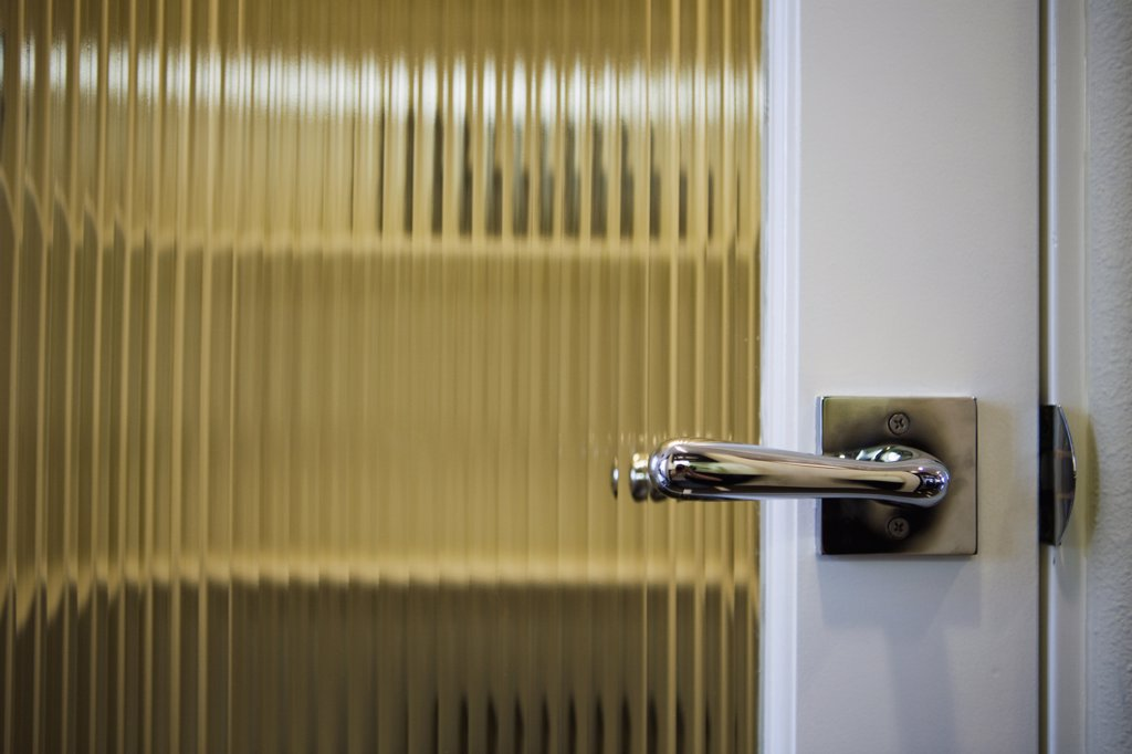 Lever style doorknob on door : Stock Photo