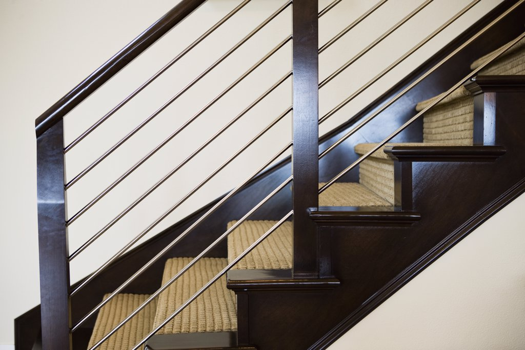 Wooden and metal handrail along carpeted staircase : Stock Photo