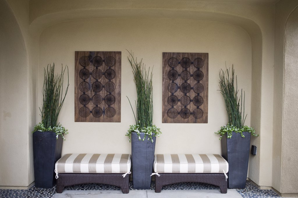 Stock Photo: 4053-2460 Wicker ottomans with cushions between potted plants on patio