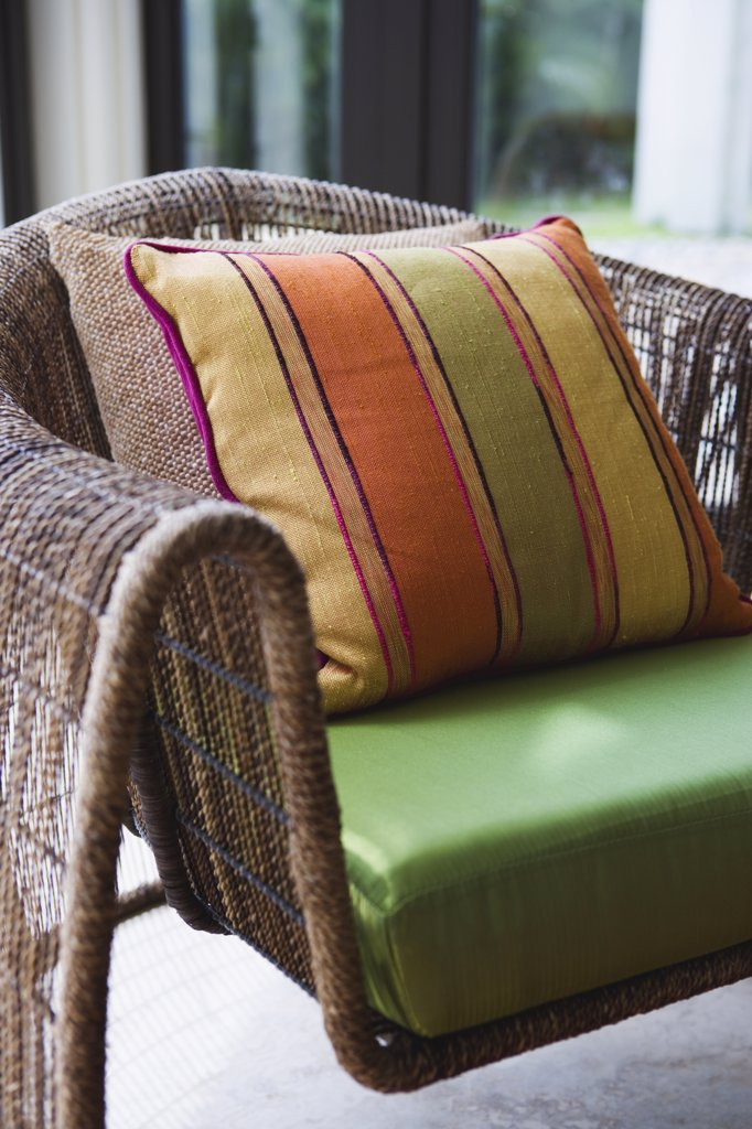Contemporary armchair with green cushion and colorful throw pillow : Stock Photo