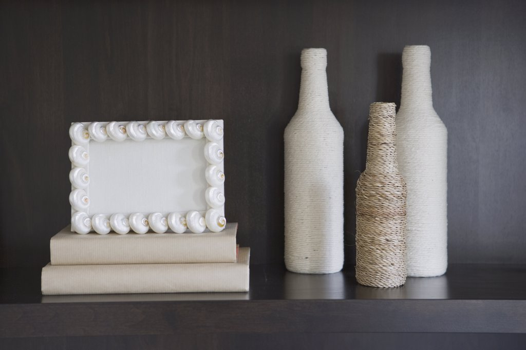 Decorative bottles and frame on bookcase : Stock Photo