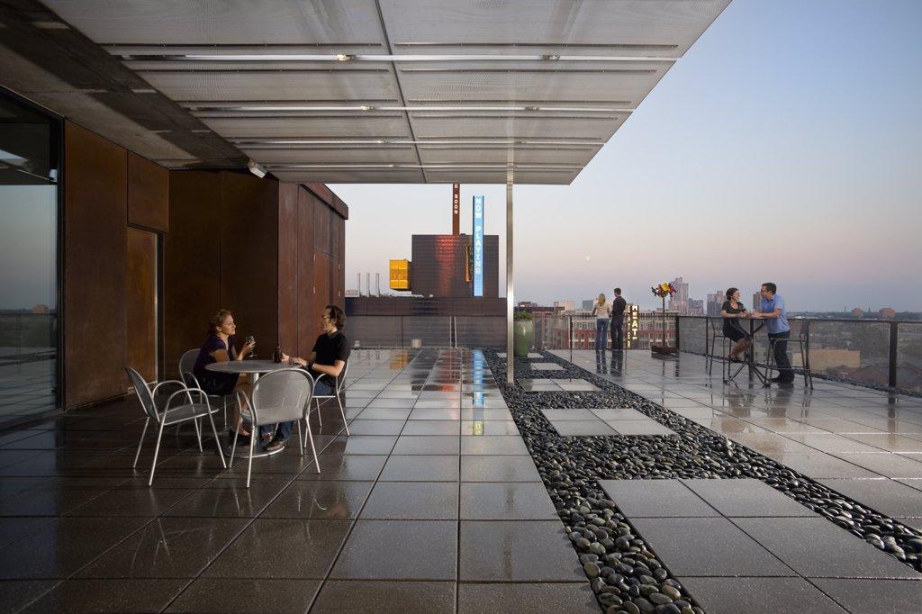 People gathered on terrace of urban loft : Stock Photo