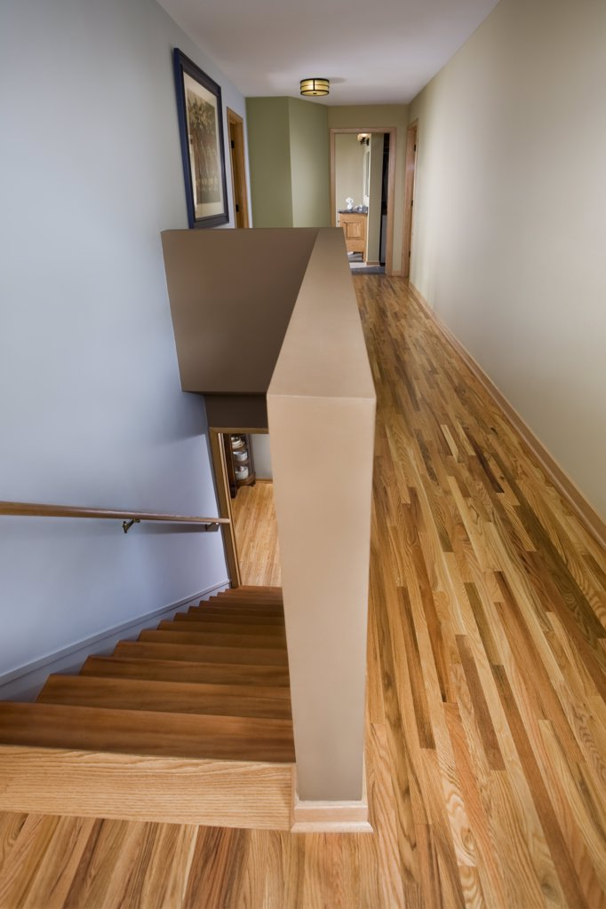 Long second floor hallway of house showing stairs : Stock Photo