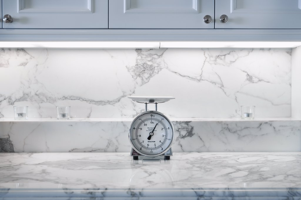 Kitchen scale on marble countertop : Stock Photo