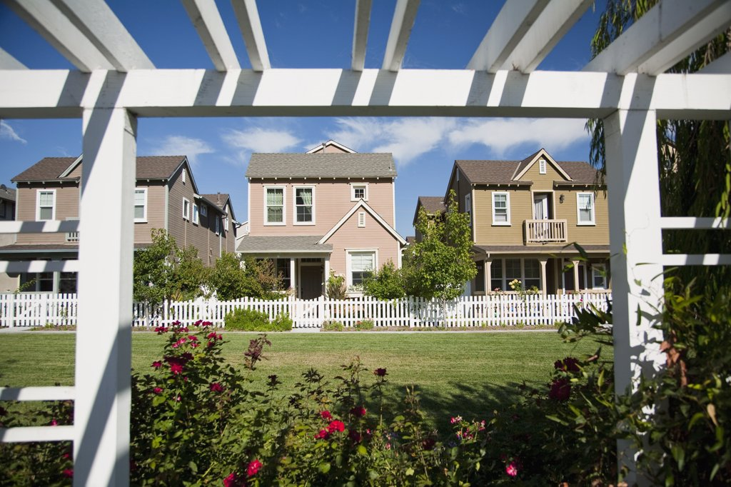 Row of homes in housing community with white picket fence : Stock Photo