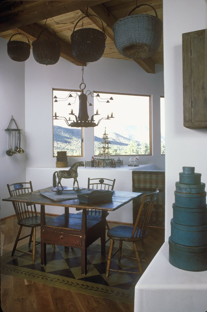 EATING AREAS: Rustic eating area with wicker baskets hanging from exposed beams. Hobby horse, blue taupe  color scheme, modern space, painted floor cloth, stack of blue shaker boxes : Stock Photo