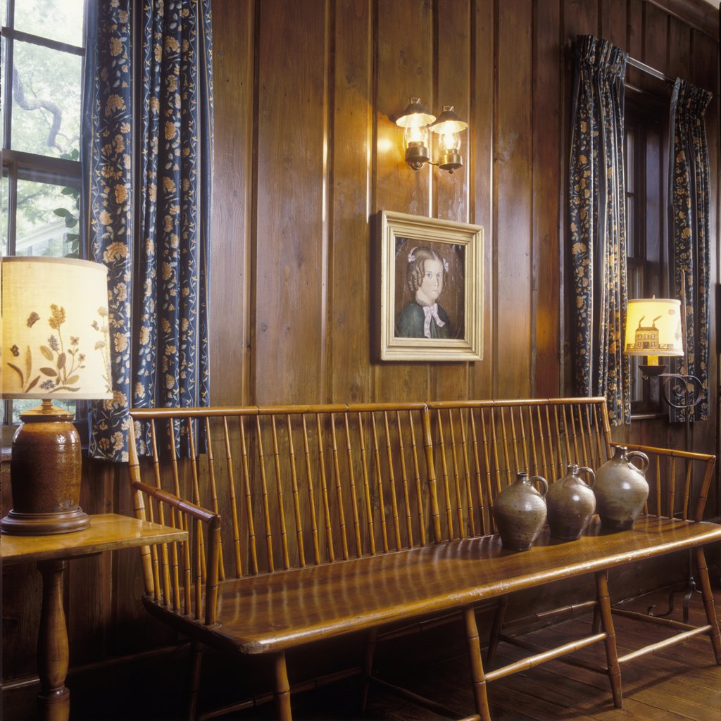 LIVING ROOM - Detail of Early American style antique bench, three pottery jugs sit on one end of bench settee, dark wood paneled walls, framed painting of a little girl, patterned pinch pleat drapes, two table lamps on either side of bench : Stock Photo