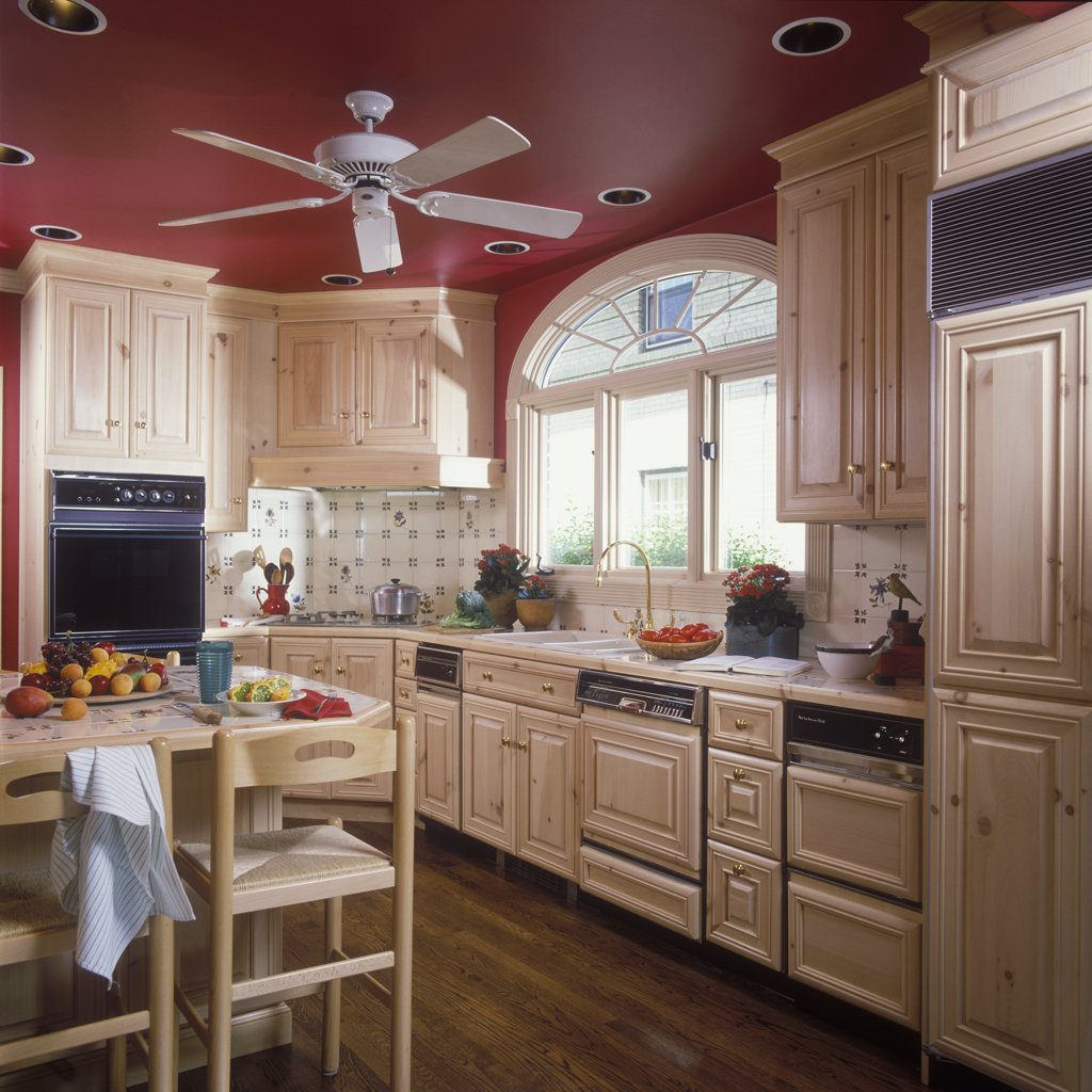 KITCHEN - Work area, island. Light wood. Sink, window with Palladian, recessed lighting ceiling fan , red painted ceiling, tile backsplash,  wood floors, custom cabinets over appliances : Stock Photo