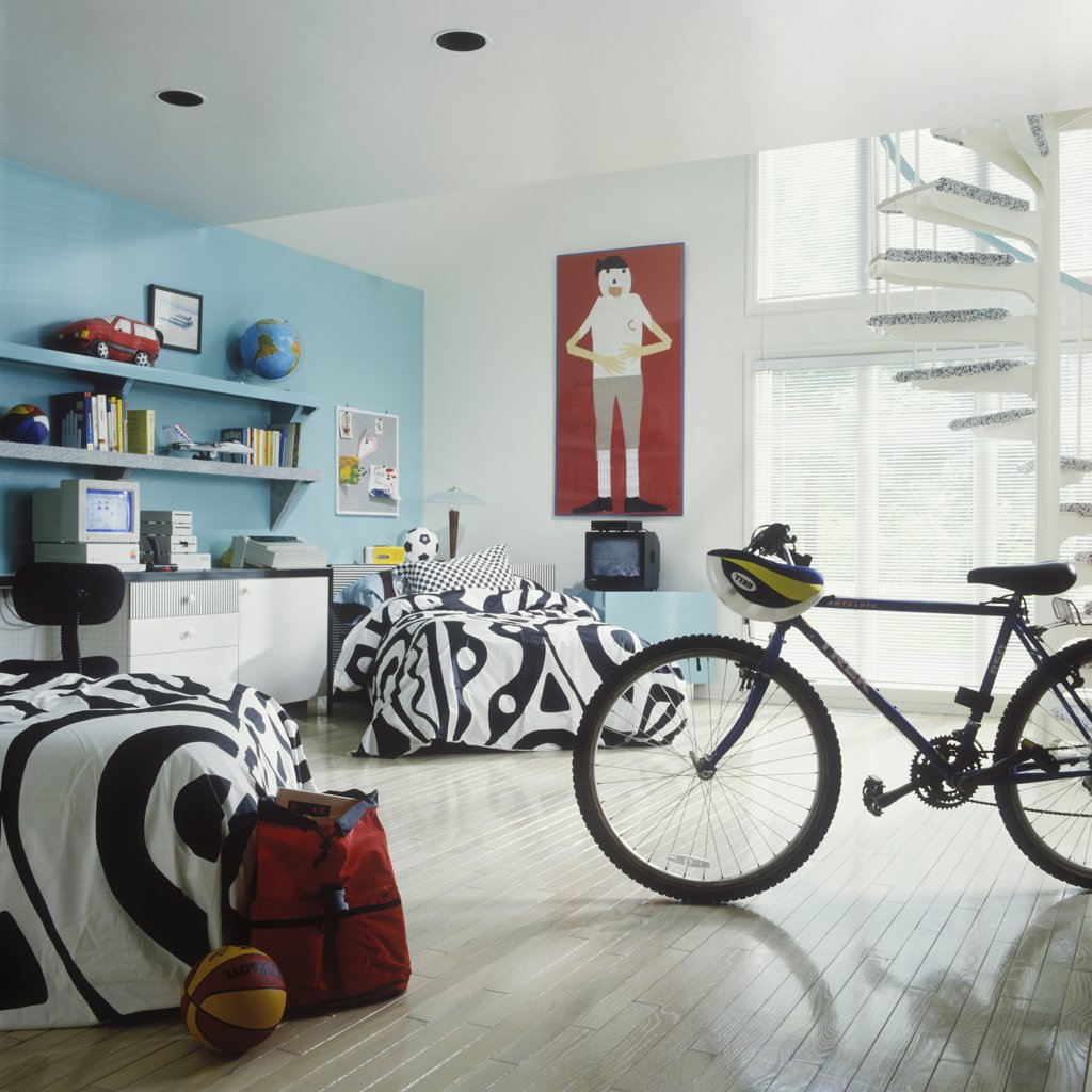 BEDROOMS - Boy's bedroom - Wall shelves, desk, white with black, red, blue wall, bicycle, geometric black and white bed spreads, spiral staircase : Stock Photo