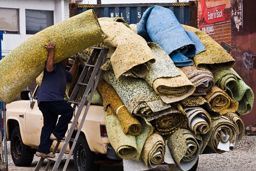 Carpet padding being loaded on a truck on the way to be recycled. Los Angeles, California, United States of America : Stock Photo