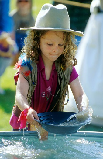Girl enthusiastically tries her hand at gold panning in a contest for children at a California Gold Rush re-enactment, Marshall's Gold Discovery State Historic Park, Coloma, California (GC) : Stock Photo