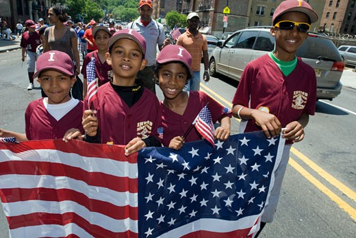 Hispanic youth league baseball players march in the oldest running Memorial Day Parade in New York  in the upper Manhattan neighborhood of Inwood on Memorial Day, Monday, May 25, 2009. Sailors and Marines joined local residents as they honored members of the armed forces that sacrificed their lives for the country. The parade, organized by the American Legion Inwood Post 581, has run for over 70 years and is the remaining Memorial Day Parade in the borough of Manhattan. : Stock Photo