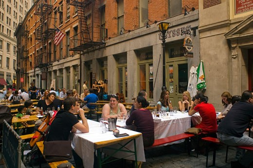 Restaurants on Stone Street in Lower Manhattan extend into the closed street. The narrow cobblestoned street is an historic district closed to vehicular traffic. (© Frances M. Roberts) : Stock Photo