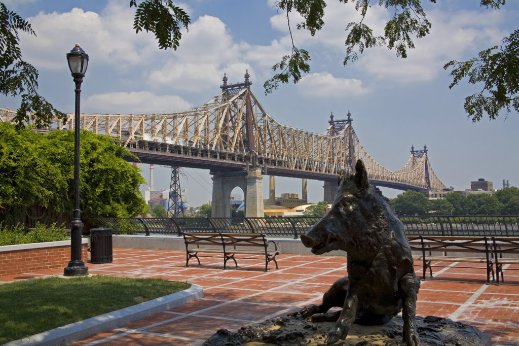 Queensboro Bridge, Sutton Place Park, Wild Boar statue, which is a replica of the bronze wild boar completed in 1634 by Renaissance sculptor Pietro Tacca (1557–1640) that stands in Florence, Italy, Manhattan, New York : Stock Photo