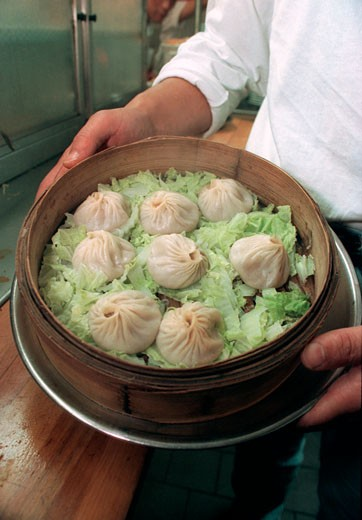 Cooked dumplings (hsiao lung bao) at Joe's Shanghai Reataurant in chinatown in New York City in a steamer on a bed of lettuce. : Stock Photo