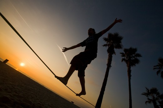Slacklining - blanacing on a slackline - Venice Beach, Los Angeles County, California, United States of America : Stock Photo