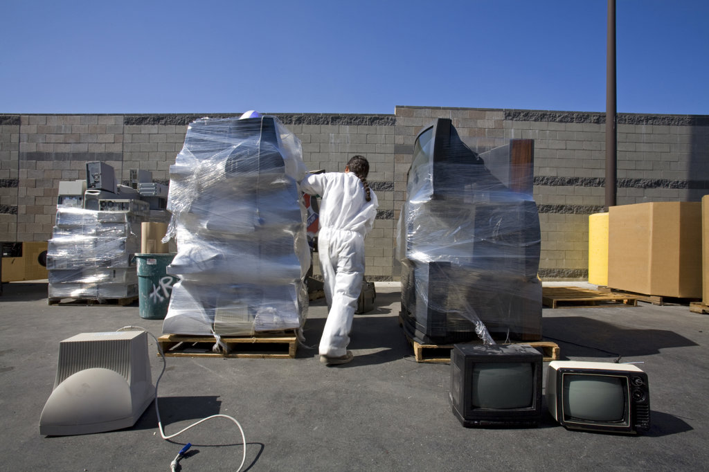 Electronic equipment, computers, stereos, TVs and even arcade games get put on pallettes and wrapped in plastic wrap. S.A.F.E Collection Center, Sun Valley, Bureau of Sanitation for the City of Los Angeles, California, USA : Stock Photo