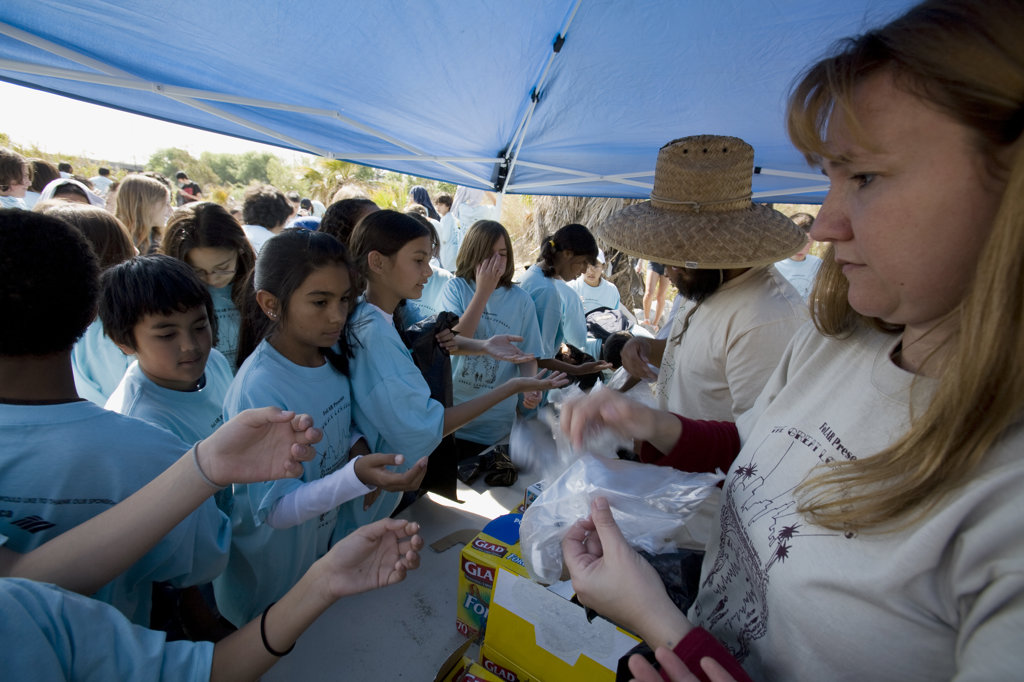 Handing our gloves and bags. Over 700 school children attended the River School Day clean up of the LA River sponsered by FoLAR (Friends of the Los Angeles River), Glendale Narrows, Los Angeles, California, USA : Stock Photo