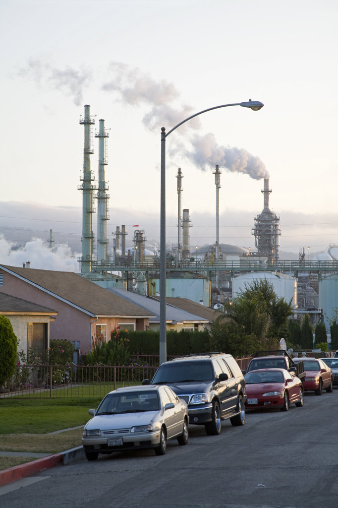 Stock Photo: 4055-5312 Residential houses next to oil refinery at Wilmington. Wilmington has one the highest risks of cancer due to it's proximity to the Port of Los Angeles at Long Beach, and the several oil refineries in the vicinity. Los Angeles, California, USA