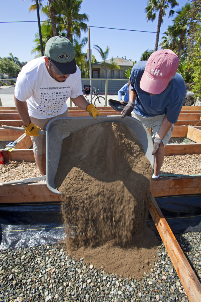 July 24, 2010. Laying down the soil for the final preparations of the planting beds at the Venice Community Garden. The 2 foot deep beds are layered with 3 inches of rocks as a buffer between the roots and the bad soil below, but will still allow water to drain. : Stock Photo