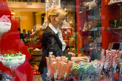 A woman shopping for sweets at the Henri Bendel store on Fifth Avenue in New York on Friday, November 20, 2009. (© Frances M. Roberts) : Stock Photo