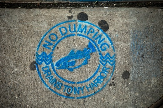A warning sign, No dumping, drains to New York harbor, seen on a sidewalk in Chinatown in Manhattan Saturday, September 4, 2010. (© Frances M. Roberts) : Stock Photo